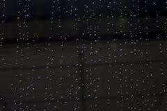 Ροή σταγονίδιων νερού στο μαύρο γυαλί στοκ εικόνες