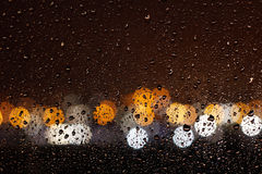 Ροή σταγόνων βροχής κάτω από το γυαλί παραθύρων τη νύχτα Στοκ εικόνα με δικαίωμα ελεύθερης χρήσης