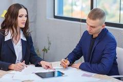 Ροή της δουλειάς στο γραφείο Ένας άνδρας και μια γυναίκα ελέγχουν τα έγγραφα γραφείων Στοκ Φωτογραφίες