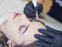 Ροή της δουλειάς φρυδιών Microblading σε ένα σαλόνι ομορφιάς Ανοικτό καφέ girl do eyebrows βελόνα στοκ φωτογραφίες