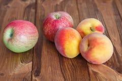 ροδάκινα και μήλα σε έναν ξύλινο πίνακα Στοκ εικόνα με δικαίωμα ελεύθερης χρήσης