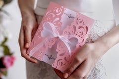 Ροζ κάρτα γαμήλιας πρόσκλησης στα χέρια της νύφης Στοκ φωτογραφία με δικαίωμα ελεύθερης χρήσης