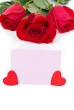 Ροζ κάρτα για τους χαιρετισμούς, τις καρδιές και τα κόκκινα τριαντάφυλλα Στοκ Εικόνα