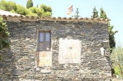 Ρολόι ήλιων και ξύλινο παράθυρο στο σπίτι πετρών Στοκ εικόνες με δικαίωμα ελεύθερης χρήσης
