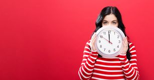 Ρολόι εκμετάλλευσης γυναικών που παρουσιάζει σχεδόν 12 Στοκ Εικόνες