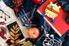 Ρολόι με τα γυαλιά και κινητό τηλέφωνο στο κόκκινο βιβλίο, έννοια εκπαίδευσης, κινητό τηλέφωνο με τα ακουστικά, φύλλο φθινοπώρου  Στοκ Φωτογραφίες