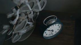 Ρολόι σε ένα σκοτεινό nightstand κοντά στον γκρίζο τοίχο Πίνακας πλευρών στο δωμάτιο απόθεμα βίντεο