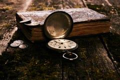 Ρολόι τσεπών με ένα παλαιό παλαιό βιβλίο και έναν αρχαίο χαλκό γ Βίβλων Στοκ Εικόνες