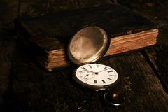 Ρολόι τσεπών με ένα παλαιό παλαιό βιβλίο και έναν αρχαίο χαλκό γ Βίβλων Στοκ εικόνα με δικαίωμα ελεύθερης χρήσης