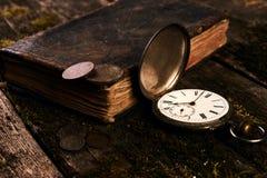Ρολόι τσεπών με ένα παλαιό παλαιό βιβλίο και έναν αρχαίο χαλκό γ Βίβλων Στοκ Φωτογραφίες