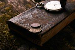 Ρολόι τσεπών με το παλαιό παλαιό βιβλίο Βίβλων και τα αναδρομικά νομίσματα Στοκ εικόνες με δικαίωμα ελεύθερης χρήσης