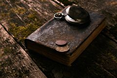 Ρολόι τσεπών με το παλαιό παλαιό βιβλίο Βίβλων και τα αναδρομικά νομίσματα Στοκ Εικόνες