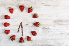 Ρολόι φραουλών με τα βέλη από τα φασόλια καφέ, που παρουσιάζουν το χρόνο στο ρολόι έξι ο ` τριάντα λεπτά ή δεκαοχτώ ώρες τριάντα  Στοκ φωτογραφία με δικαίωμα ελεύθερης χρήσης