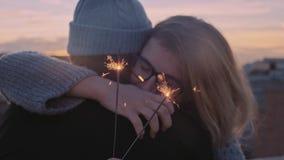 Ρομαντικά αγκαλιάσματα χειμερινών ζευγών με τα sparklers απόθεμα βίντεο