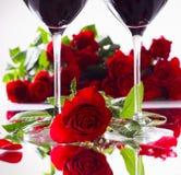 Ρομαντικά κόκκινα τριαντάφυλλα με δύο ποτήρια του κόκκινου κρασιού Στοκ Εικόνες
