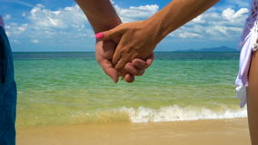 Ρομαντικά χέρια λαβής ζεύγους στην παραλία φιλμ μικρού μήκους