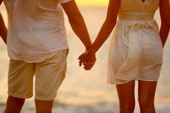 Ρομαντικά χέρια εκμετάλλευσης ζευγών στο ηλιοβασίλεμα παραλιών Στοκ εικόνα με δικαίωμα ελεύθερης χρήσης