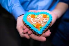 Ρομαντικά χέρια που κρατούν διαμορφωμένο το καρδιά κέικ Στοκ Εικόνα