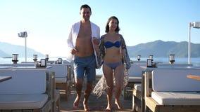 Ρομαντικές διακοπές, ευτυχές ζευγάρι που τρέχουν μαζί στην αποβάθρα εν πλω το καλοκαίρι απόθεμα βίντεο