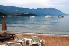 Ρομαντική άποψη σχετικά με την παραλία, τα βουνά, τις καρέκλες και τη θάλασσα με τις βάρκες Στοκ Εικόνες