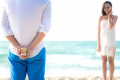Ρομαντική έννοια με το άτομο που κρατά το άσπρο δαχτυλίδι που κάνει την πρόταση γάμου στην παραλία Ασιατικός μήνας του μέλιτος ερ στοκ εικόνα με δικαίωμα ελεύθερης χρήσης