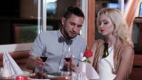 Ρομαντική ατμόσφαιρα, άνδρας και γυναίκα κατά μια ημερομηνία σε ένα εστιατόριο, ένα ρομαντικό βραδυνό σε ένα εστιατόριο, ένας σύζ απόθεμα βίντεο