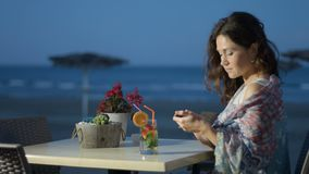 Ρομαντική γυναίκα που απολαμβάνει το υπόλοιπο στο εστιατόριο παραλιών, που στέλνει το μήνυμα από το τηλέφωνο απόθεμα βίντεο