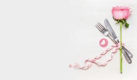 Ρομαντική επιτραπέζια θέση γευμάτων που θέτει με το σύμβολο τριαντάφυλλων και καρδιών στο ελαφρύ υπόβαθρο, τοπ άποψη, έμβλημα Στοκ Εικόνα