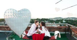 Ρομαντική ημερομηνία στη στέγη Το ευτυχές όμορφο αγαπώντας ζεύγος κρατά τα χέρια και φιλά tenderly 4k μήκος σε πόδηα απόθεμα βίντεο