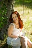 Ρομαντική κοκκινομάλλης γυναικεία συνεδρίαση στη χλόη, βιβλίο ανάγνωσης Στοκ εικόνα με δικαίωμα ελεύθερης χρήσης