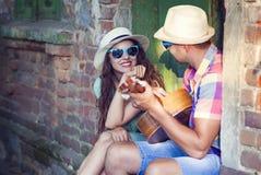Ρομαντική νέα κιθάρα παιχνιδιού ζευγών υπαίθρια Στοκ Φωτογραφίες