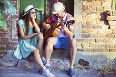 Ρομαντική νέα κιθάρα παιχνιδιού ζευγών υπαίθρια Στοκ Εικόνες