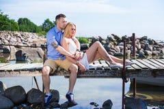 Ρομαντική νέα συνεδρίαση ζευγών στην αποβάθρα και απόλαυση της θέας θάλασσας Στοκ Φωτογραφία