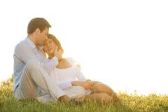 Ρομαντική νέα συνεδρίαση ζευγών στη χλόη ενάντια στο σαφή ουρανό Στοκ Φωτογραφία