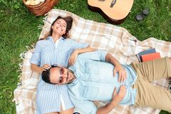 Ρομαντική νέα χαλάρωση ζευγών σε ένα πάρκο Στις πλάτες τους σε ένα κάλυμμα πικ-νίκ, αγκαλιά στοκ φωτογραφία με δικαίωμα ελεύθερης χρήσης