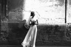 Ρομαντική πανέμορφη νύφη χεριών εκμετάλλευσης πολυτέλειας στο υπόβαθρο ο Στοκ Εικόνα