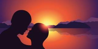 Ρομαντική σκιαγραφία φιλιών στην όμορφα λίμνη ηλιοβασιλέματος και το τοπίο βουνών ελεύθερη απεικόνιση δικαιώματος