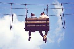 Ρομαντική συνεδρίαση στους ουρανούς, ταλαντεύοντας πόδια συνεδρίασης ζευγών σε έναν κρεμώντας πάγκο στοκ εικόνες