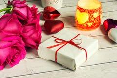 Ρομαντική σύνθεση με το ροδαλό υπόβαθρο ημέρας λουλουδιών, βαλεντίνων του ST κεριών και δώρων Στοκ εικόνα με δικαίωμα ελεύθερης χρήσης