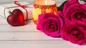 Ρομαντική σύνθεση με το ροδαλό υπόβαθρο ημέρας λουλουδιών, βαλεντίνων του ST κεριών και δώρων Στοκ Φωτογραφίες