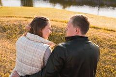 Ρομαντική χαλάρωση ζευγών στην αποβάθρα ποταμών στο πάρκο φθινοπώρου Στοκ Εικόνες