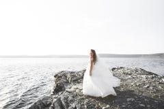 Ρομαντική όμορφη νύφη στην άσπρη τοποθέτηση φορεμάτων στη θάλασσα υποβάθρου Στοκ Φωτογραφία