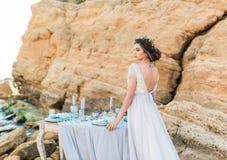 Ρομαντική όμορφη νύφη στην τοποθέτηση φορεμάτων πολυτέλειας στην παραλία Στοκ Φωτογραφία