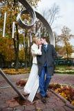Ρομαντικοί νύφη και νεόνυμφος φιλιών στο πάρκο φθινοπώρου Στοκ Φωτογραφίες