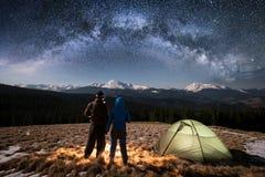 Ρομαντικοί τουρίστες ζευγών που απολαμβάνουν στη στρατοπέδευση τη νύχτα κάτω από το όμορφο σύνολο νυχτερινού ουρανού των αστεριών Στοκ εικόνες με δικαίωμα ελεύθερης χρήσης