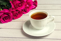 Ρομαντικός βαλεντίνος ` s του ST που θέτει με το φλυτζάνι τσαγιού και τα κόκκινα τριαντάφυλλα Στοκ Φωτογραφίες