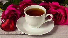 Ρομαντικός βαλεντίνος ` s του ST που θέτει με το φλυτζάνι τσαγιού και τα κόκκινα τριαντάφυλλα Στοκ Εικόνα