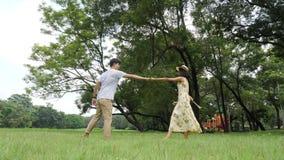 Ρομαντικό ασιατικό ζεύγος που χορεύει στον κήπο με την ευτυχή συγκίνηση φιλμ μικρού μήκους