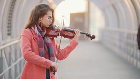 Ρομαντικό βιολί παιχνιδιού γυναικών στην υπερυψωμένη μετάβαση απόθεμα βίντεο