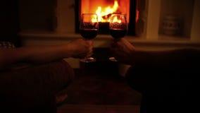 Ρομαντικό βράδυ ζευγών με τα ποτήρια του κρασιού στο άνετο σπίτι κοντά στην εστία φιλμ μικρού μήκους